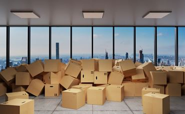 large industrial urban warehouse large pile of cardboard moving boxes in front of Skyline, conceptual 3D Illustration