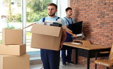 Umzugshelfer tragen Kisten aus der Firma