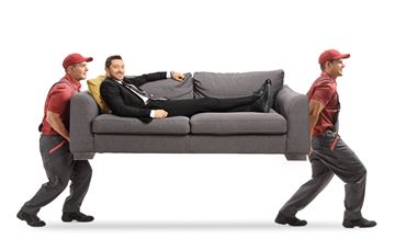 Movers carrying a sofa with a man in a suit relaxing on the sofa isolated on white background