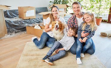 Glückliche Familie mit zwei Kindern und Hund im neuen Haus nach Umzug