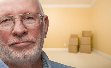 Sad Older Man In Empty Room with Boxes - Concept for Foreclosure, Diviorce, Moving, etc.