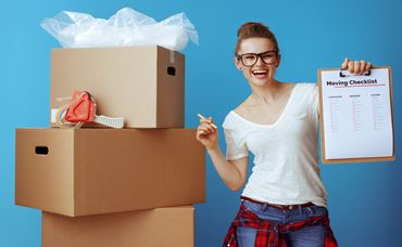 happy modern woman in white t-shirt near cardboard box showing moving checklist against blue background