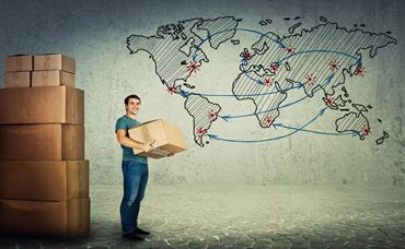 Full length portrait of smiling delivery worker carrying a big cardboard box from stack, global shipping and delivery over world map sketch. Mail order distribution.