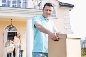 Familie bringt Umzugskartons in ihr neues Zuhause