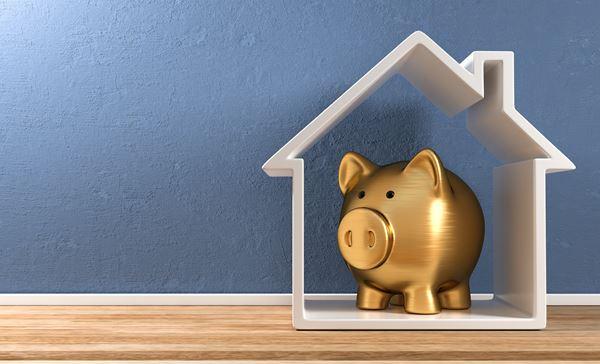 Sparschwein steht in Haus-Silhouette