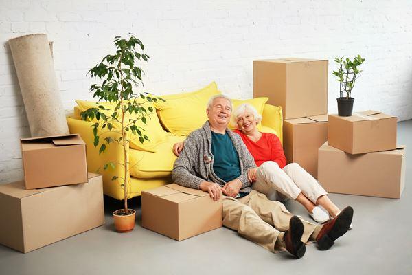 Senioren sitzen vor Umzugskartons auf dem Boden