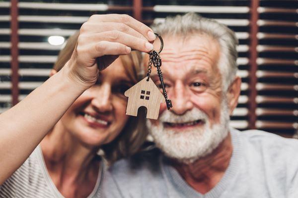 Seniorenpaar zeigt Schlüssel der neuen Wohnung