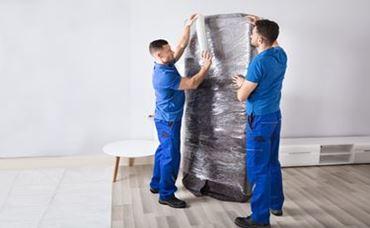 Umzugshelfer transportieren ein Möbelstück